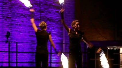 Zwei Artisten spielen Feuerpoi.