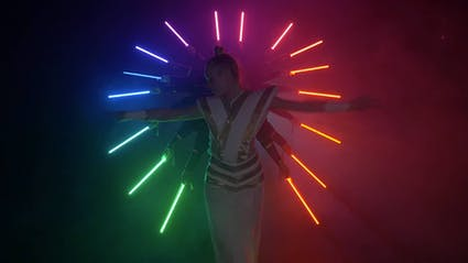 Performer in a white costume with extended arms, surrounded by a colorful circle of LED-tools.