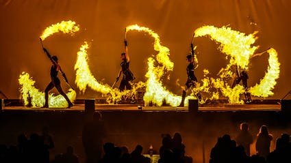 Fireshow with big flames and fire breathing on a stage with audience