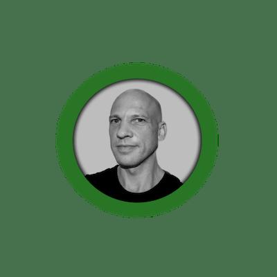 Black/white profile image of member Thomas in a green circle.