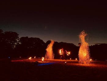 Fireshow at night with big sparcle effect and firejuggler.