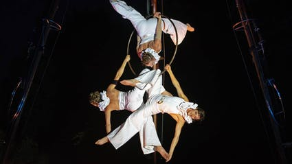 Three aerial acrobats hanging on a ring extending arms and legs.