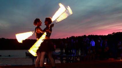 Zwillinge spielen Feuershow vor einem See.