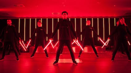 Dance formation in red light holding LED-tools .