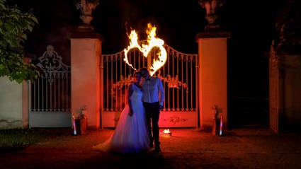 Bridal couple at a fireshow with burning fire-heart.
