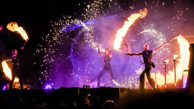 Stage show with circus artists creating flame and spark effects.