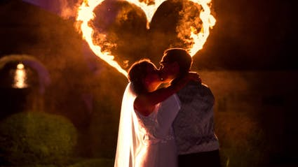 Fireshow on a wedding with fireheart and kissing bride and broom.