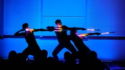 Three Light artists in a pose with light sticks with audience in the front.