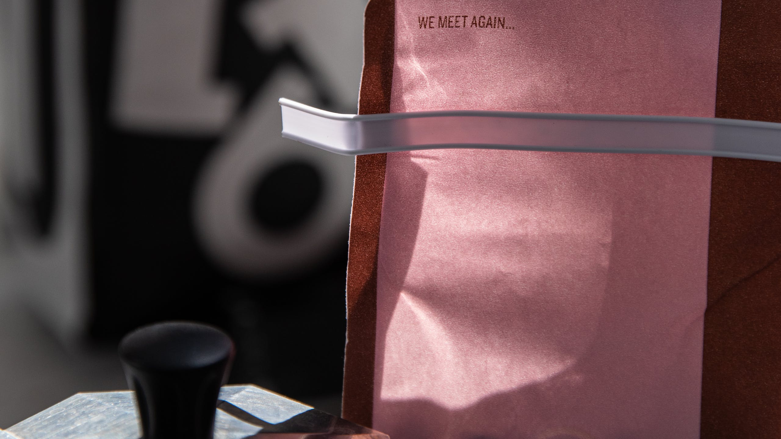 "Close up of pink coffee bag saying ""We meet again..."""