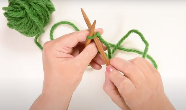 Insert the tip of the right needle into the slip knot and cross it behind the left needle to start basic cast on
