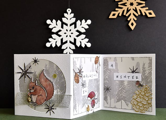 stamped and cut out squirrel holding an acorn. Placed in a circular cut out with a winter backdrop