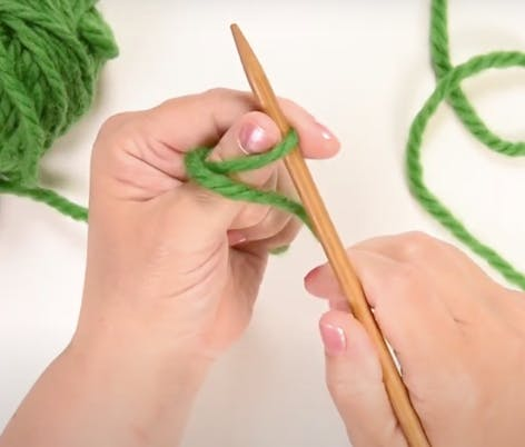 wrap the yarn around your thumb and insert needle under the loop for long tail cast on