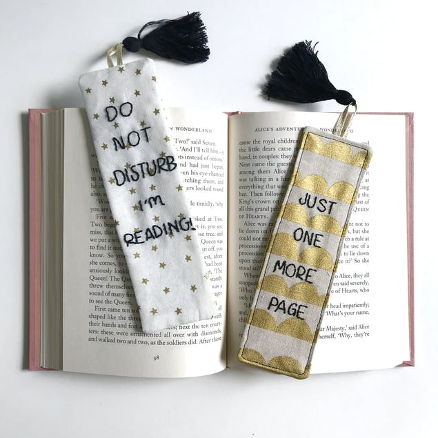 Two fabric bookmarks embroidered in black thread, resting on an open book. One reads 'Do Not Disturb, I'm reading', the second one reads 'Just one more page'