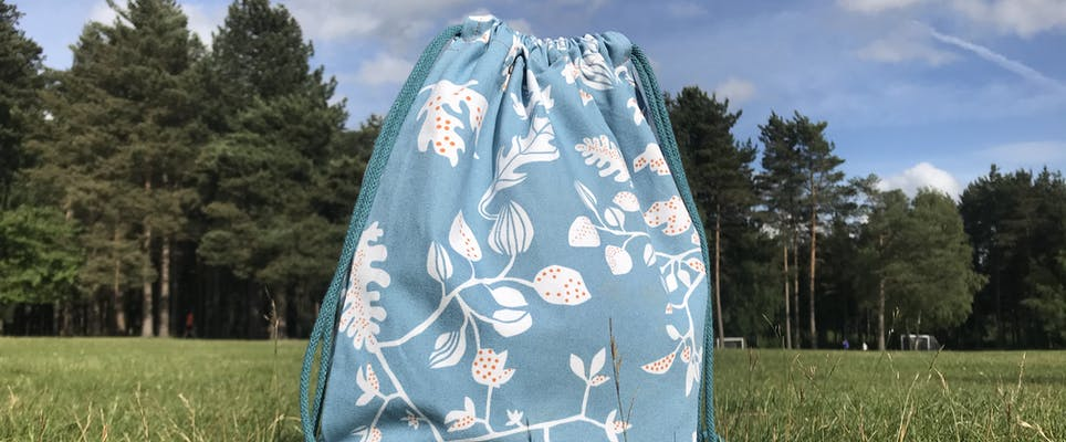 Drawstring bag in blue floral cotton in an open field with blue skies