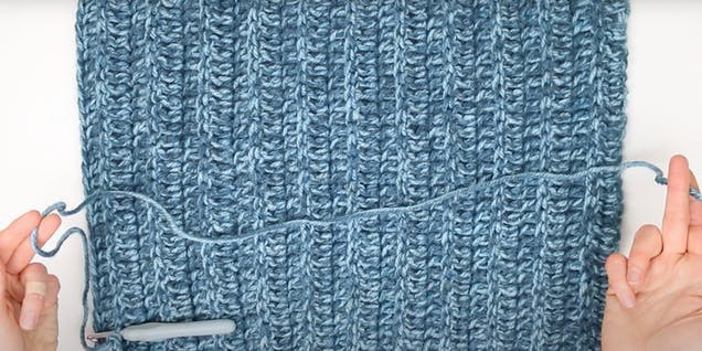 flat lay of crocheted square with long yarn tail ready to sew