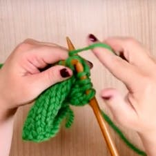 bring yarn around right needle to knit