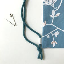 Cord handle fastened in knot and secured to the bag with ribbon loop