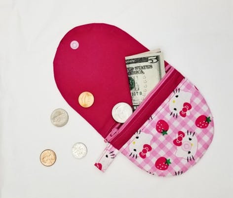 sewn coin purse with zip compartment, lined with plastic popper close