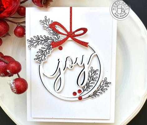 die cut bauble card design with joy cut out in the centre