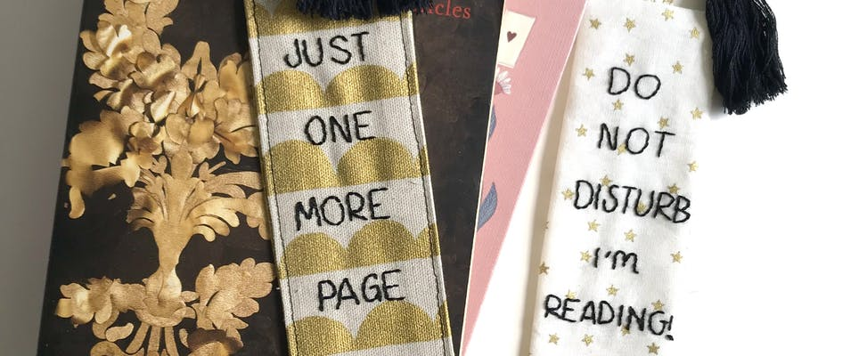Two fabric bookmarks resting on books