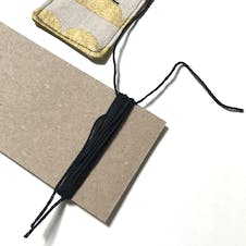 Embroidery thread wrapped around card to make tassel