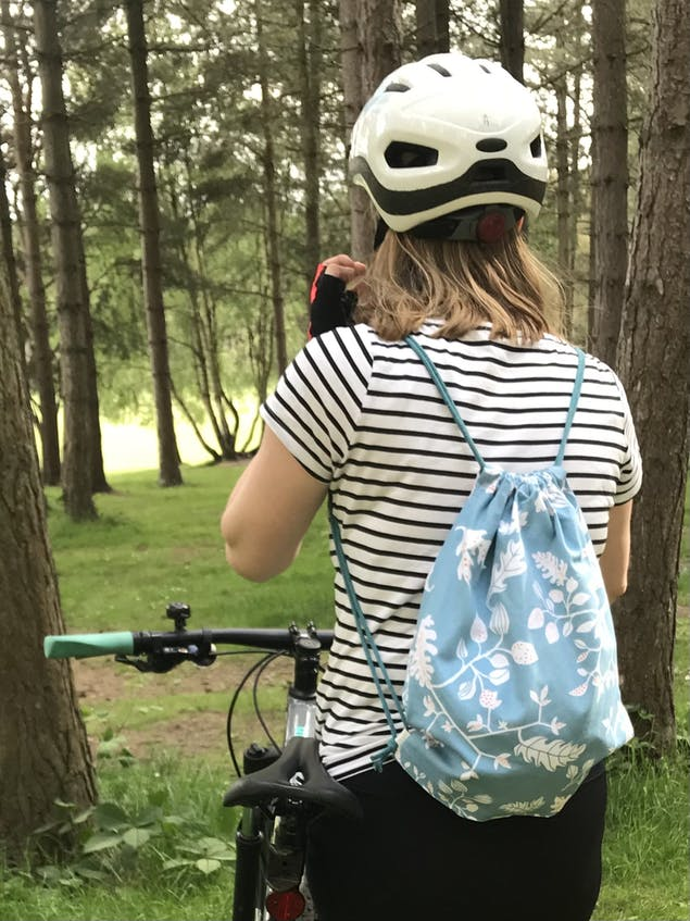 Woman wearing a striped t shirt, bike helmet and a drawstring bag with her back to the camera next to a bike