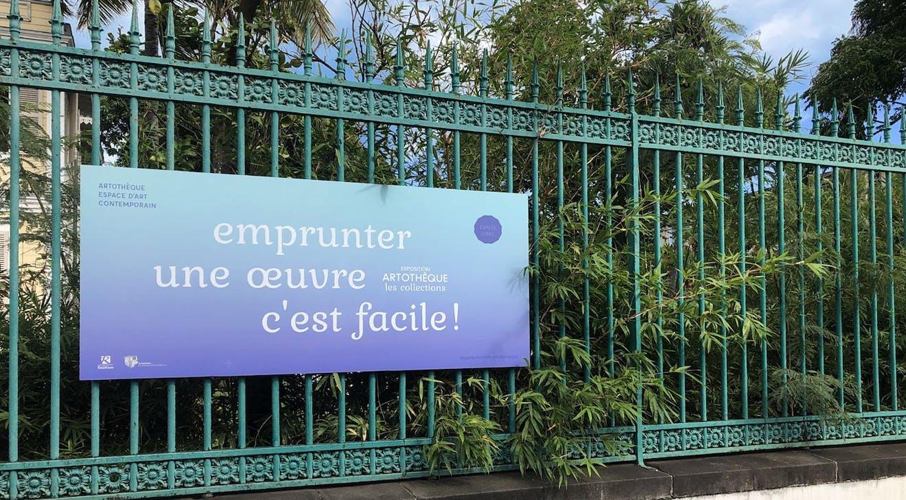 """graphisme pour la campagne """"emprunter une œuvre c'est facile !"""" de l'Artothèque. Panneau accroché sur la clôture dans la rue de Paris, Saint-Denis, île de La Réunion."""