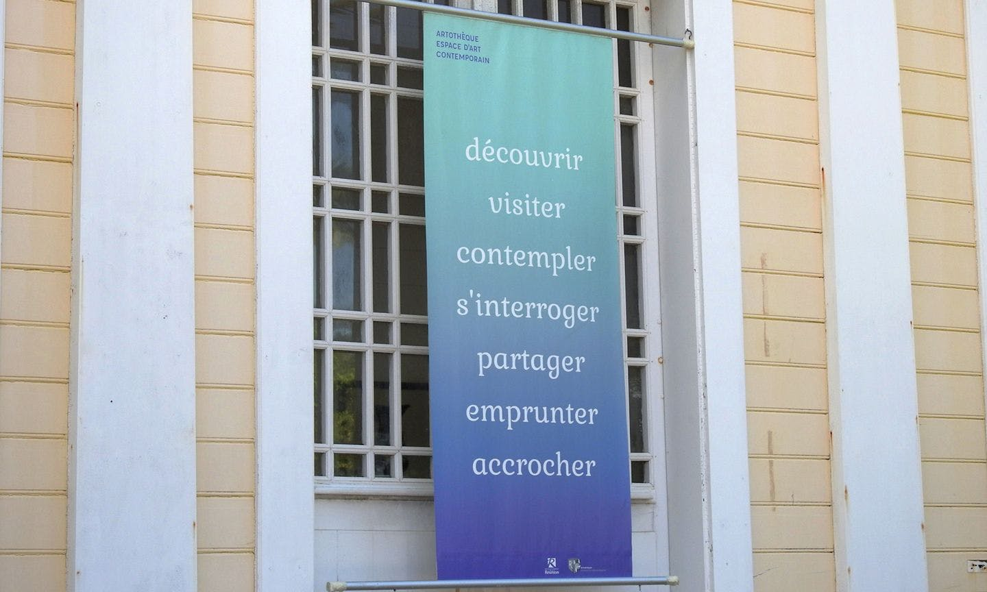 close-up of the graphic design of a blue banner with white text hanging on the Artothèque (Art Library) de la Réunion building