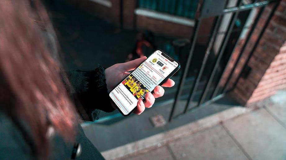 Foto von Frau mit langen Haaren, die ein iPhone mit kicker News in der Hand hält.