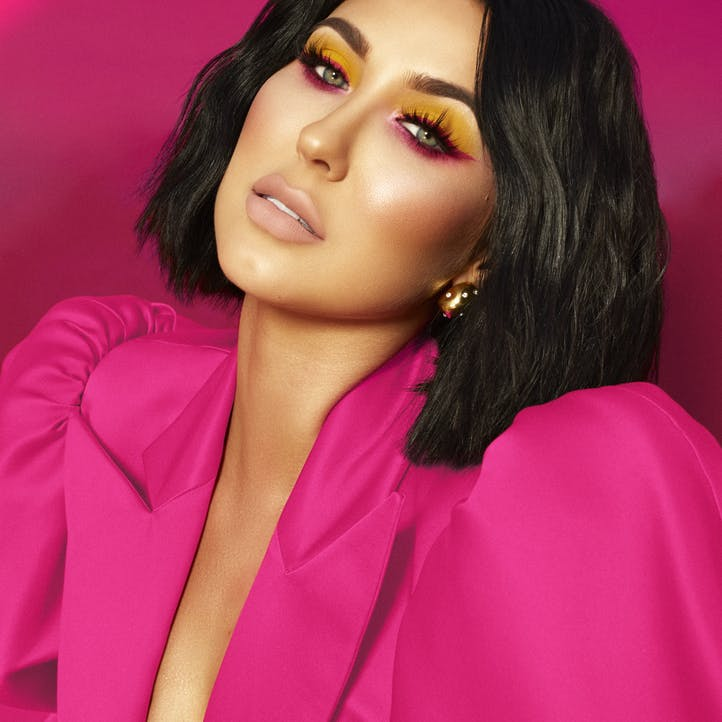 Jaclyn Hill close up in vibrant fuchsia outfit with color coordinated eye shadow from Morphe X Jaclyn Hill palette and complimentary cheeks and lips.