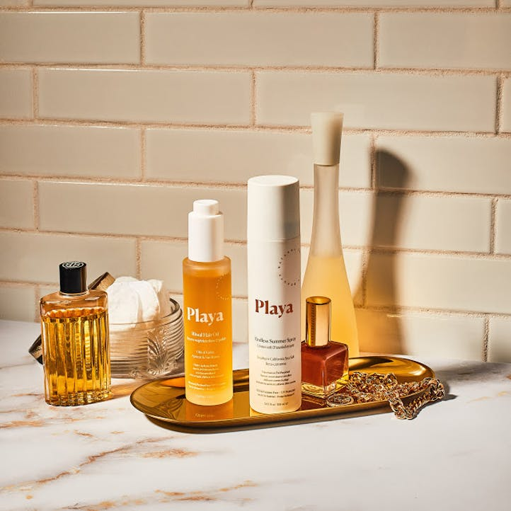 Image of bottle of Playa Ritual Hair Oil and Endless Summer Spray hair texture on vanity with perfumes.