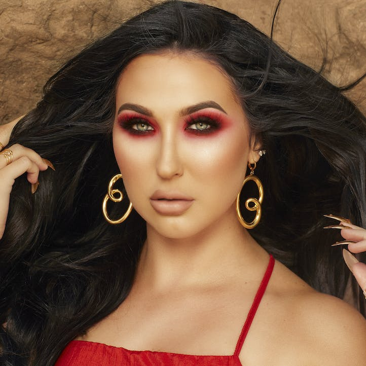 Jaclyn Hill close up in red outfit with color coordinated eye shadow Morphe X Jaclyn Hill palette and complimentary cheeks and lips.
