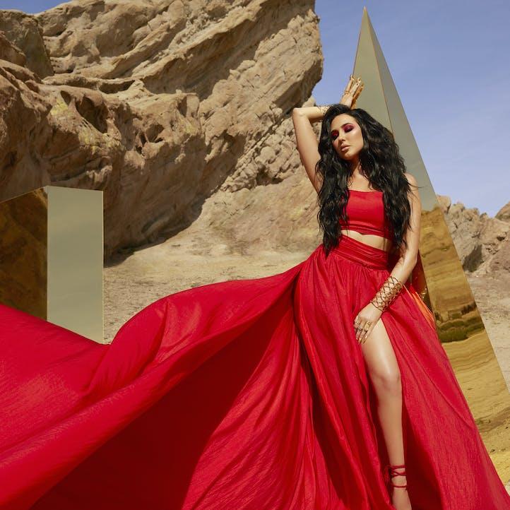 Jaclyn Hill posing in desert in flowing red dress against blue skies. Coordinating makeup look from Morphe X Jaclyn Hill palette.