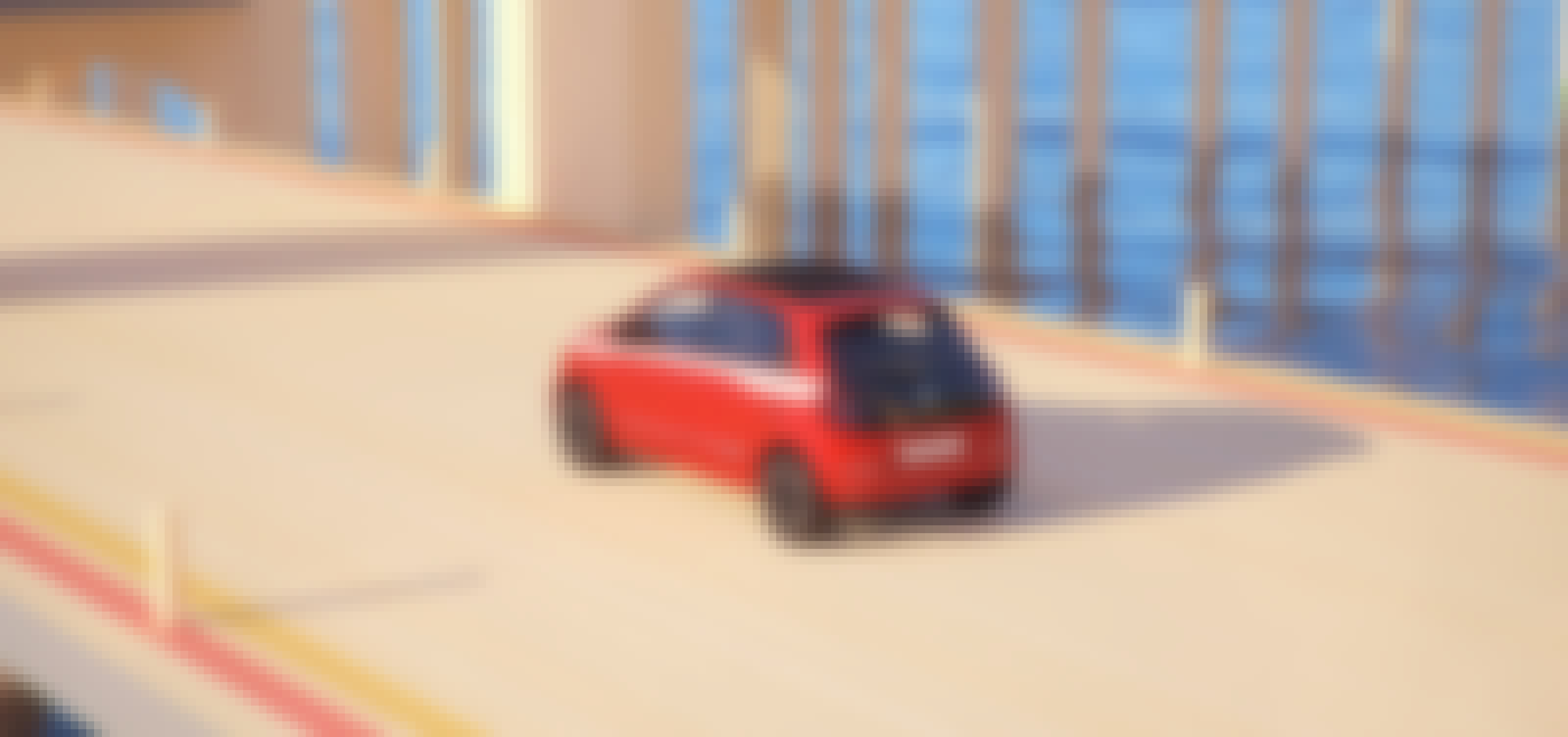 A red Renault Twingo model on the road.