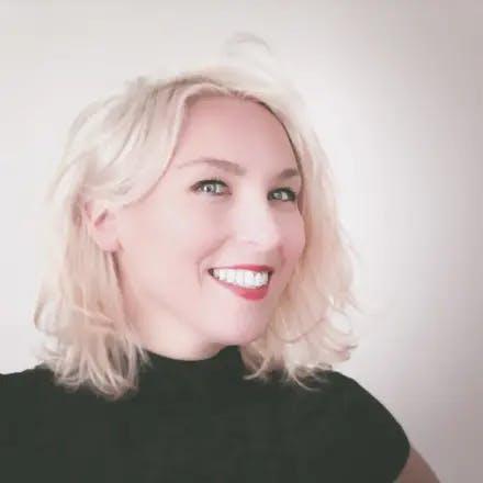Portret van een vrolijk lachende jonge blonde vrouw in een zwarte top en een witte achtergrond