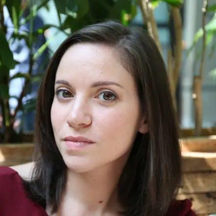 Portretfoto van een jonge blanke vrouw met donkerbruin haar en planten op de achtergrond