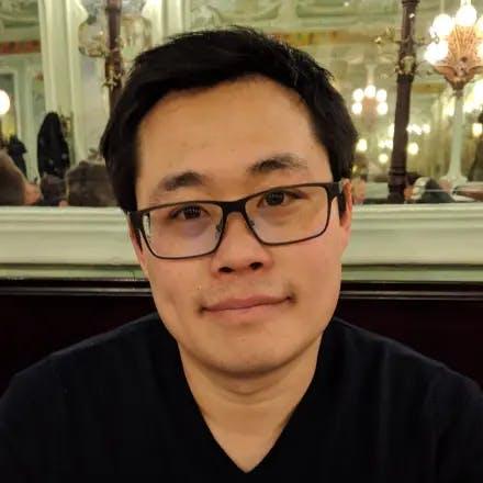 Portretfoto van een Aziatische jongeman met een bril in een restaurant