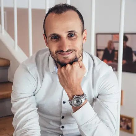 Portretfoto van een Mediterraan uitziende jongeman met een baardje en een wit overhemd tegen de achtergrond van een witte trap