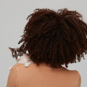 Woman holding a kitten over her shoulder