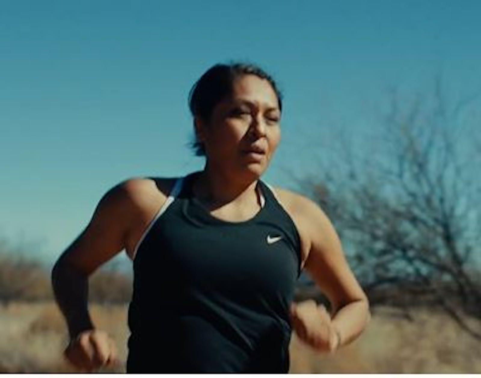 Woman in black tank top running in desert