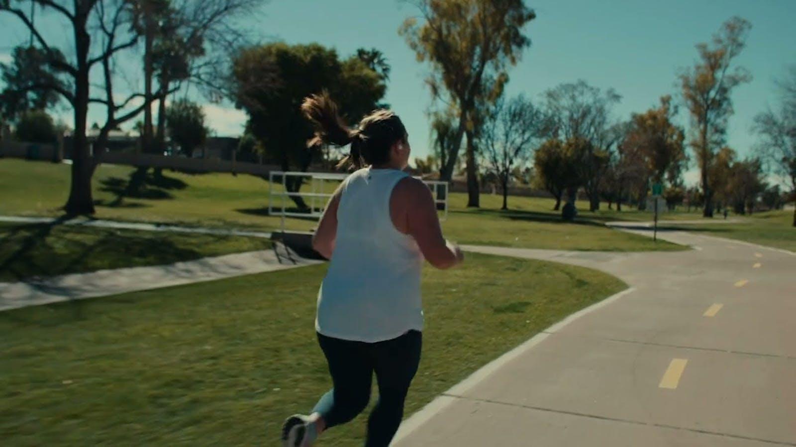 Woman in white tank top running down empty street