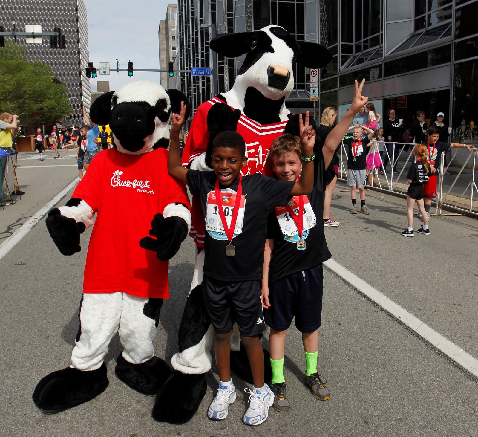 Chick Fil A's mascots with two cheering children in street