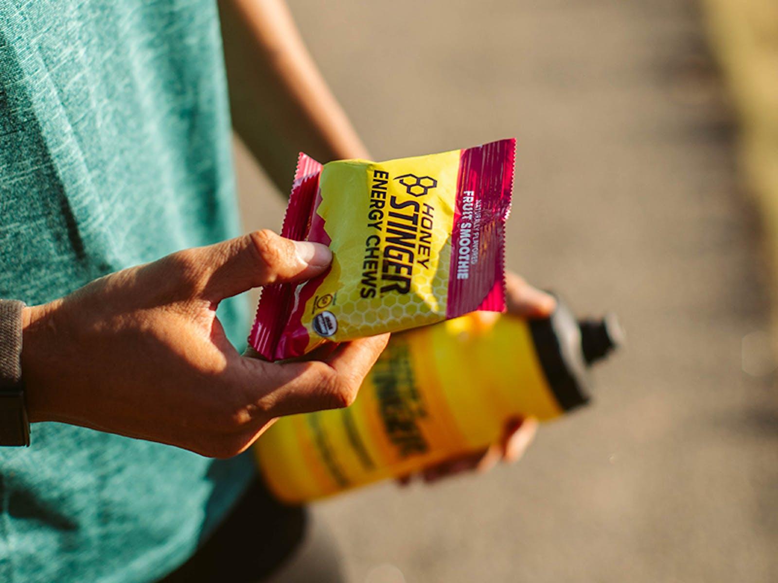 Holding Honey Stinger energy chews and wattle bottle
