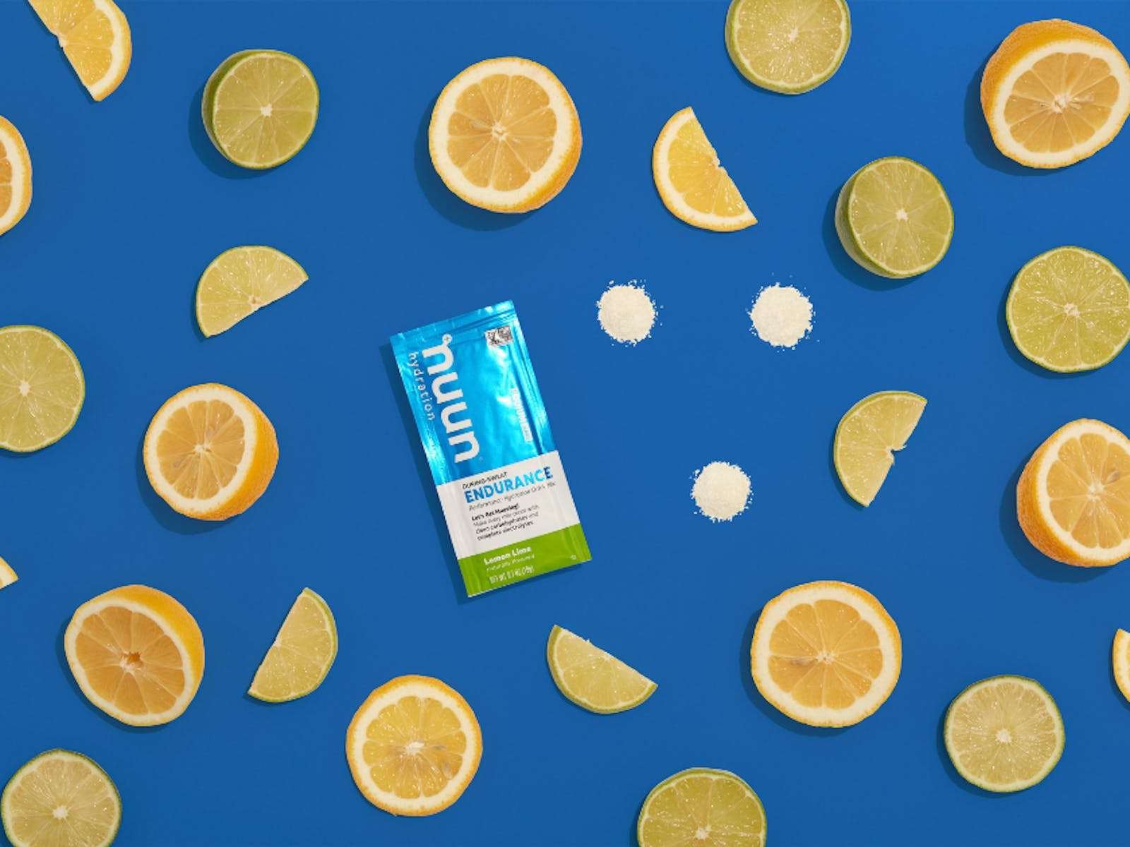 Packet of nuun against blue background full of limes and lemons