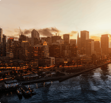 A city scene shows the bustling economic activity amidst a bright, glowing yellow sunset