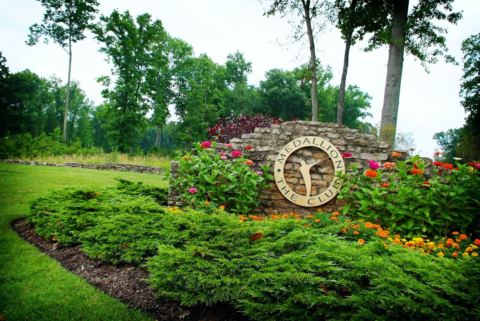 Image of The Medallion Club entry sign with flowers in bloom.