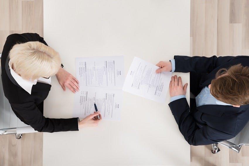 deux personnes assises en face et discutant sur des documents