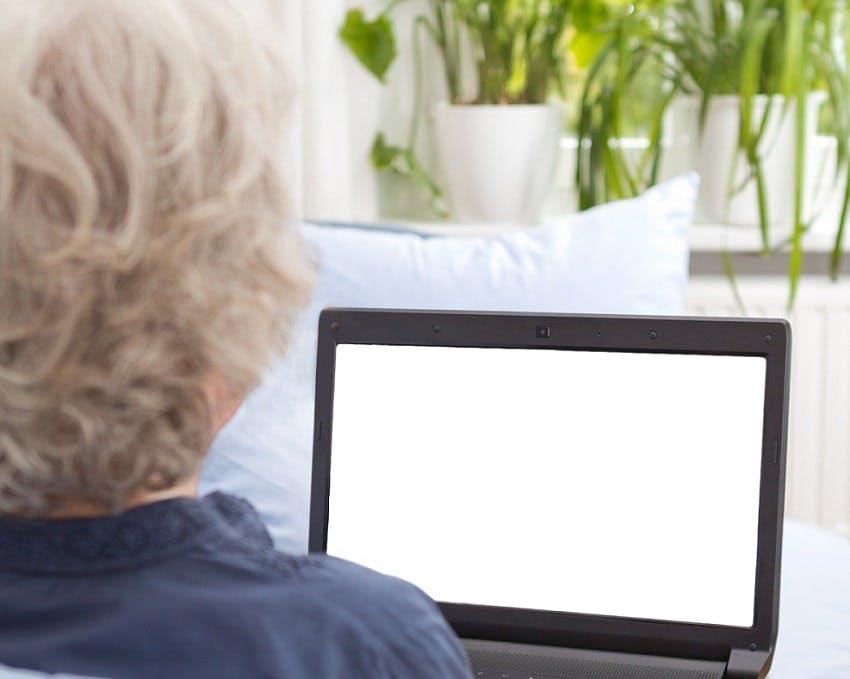 femme sénior vue de dos devant ordinateur portable