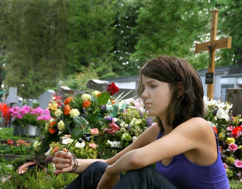 jeune fille assise à côté d'une tombe et tenant une rose rouge