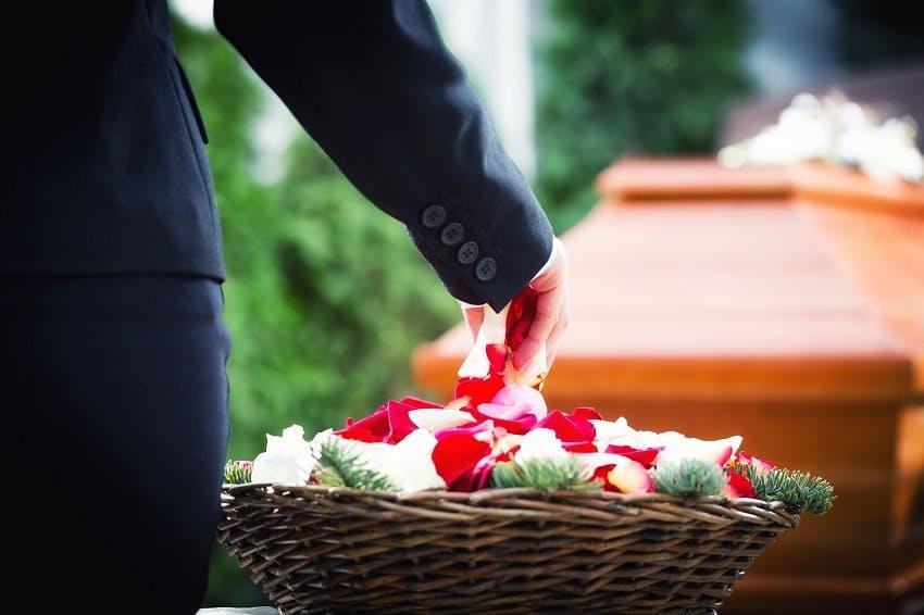 personne prenant des pétales de rose d'un panier à côté d'un cercueil